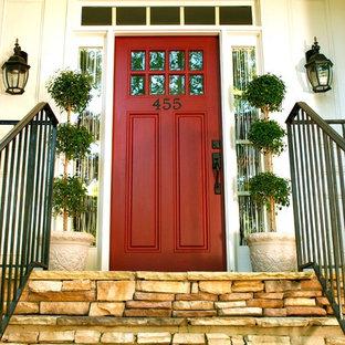 Exemple d'une entrée chic avec une porte rouge.