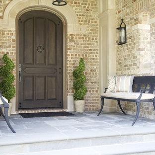 Inspiration pour une entrée traditionnelle avec une porte simple et une porte en bois foncé.