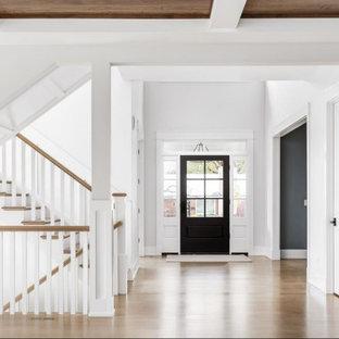 Foto på en stor lantlig foajé, med vita väggar, ljust trägolv, en svart dörr och brunt golv