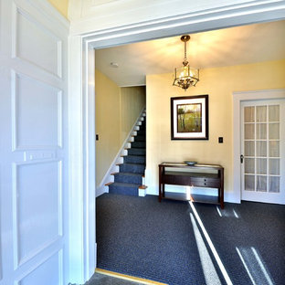 Transitional slate floor entryway photo in Boston with yellow walls and a glass front door