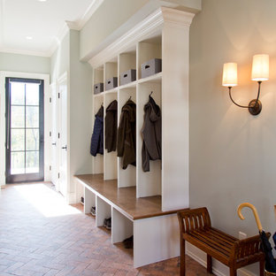 セントルイスの大きい片開きドアトランジショナルスタイルのおしゃれなマッドルーム (グレーの壁、レンガの床、黒いドア、赤い床) の写真