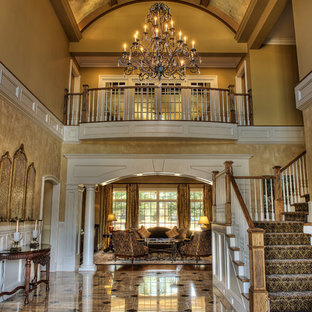 Expansive traditional foyer in Other with yellow walls and limestone floors.