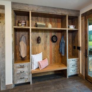 Inspiration pour une entrée chalet de taille moyenne avec un vestiaire, un mur blanc, un sol en carrelage de porcelaine, une porte simple, une porte en bois foncé et un sol gris.