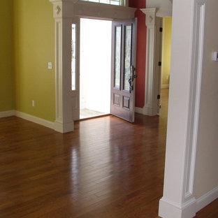 Cette image montre une petit porte d'entrée bohème avec un mur vert, une porte simple, une porte en bois foncé et un sol en bois clair.