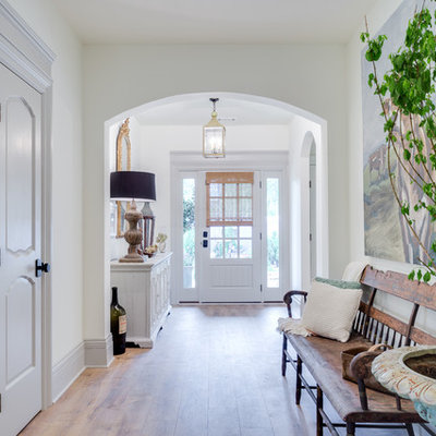 Entryway - mid-sized transitional medium tone wood floor and brown floor entryway idea in Orange County with white walls and a white front door