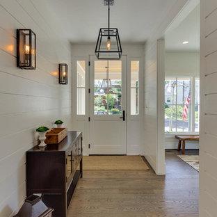Idéer för att renovera en stor amerikansk foajé, med vita väggar, mellanmörkt trägolv, en vit dörr och en enkeldörr