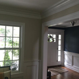 Cette photo montre une porte d'entrée chic de taille moyenne avec un mur bleu, un sol en bois brun, une porte simple et une porte blanche.