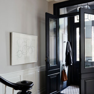Example of a transitional medium tone wood floor entryway design in New York with gray walls and a black front door
