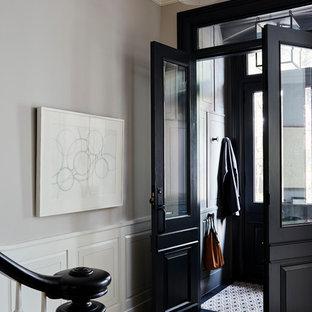 Immagine di un ingresso con vestibolo tradizionale con pareti grigie, pavimento in legno massello medio, una porta a due ante e una porta nera