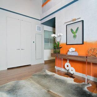 Exempel på en mellanstor modern foajé, med orange väggar, mellanmörkt trägolv, en dubbeldörr och en grå dörr