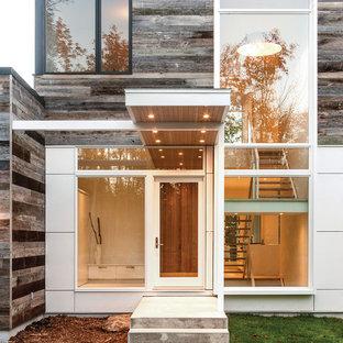 Ejemplo de puerta principal actual, grande, con puerta simple, puerta de vidrio, paredes blancas y suelo de madera clara