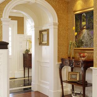 Ornate medium tone wood floor entryway photo in Boston with yellow walls