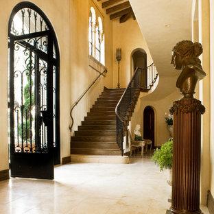 Entryway - mediterranean travertine floor and beige floor entryway idea in Santa Barbara with beige walls and a black front door