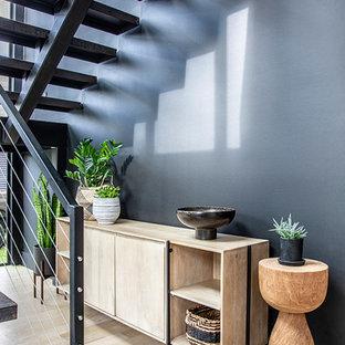 Idée de décoration pour une grand porte d'entrée design avec un mur noir, un sol en bois clair, une porte simple, une porte métallisée et un sol marron.