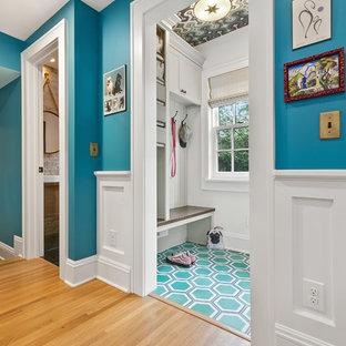 Inredning av ett eklektiskt mellanstort kapprum, med grå väggar, grönt golv och en vit dörr