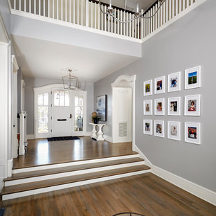 Example of a large coastal medium tone wood floor and multicolored floor entryway design in San Diego with gray walls and a white front door