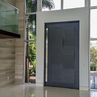 Стильный дизайн: большая входная дверь в стиле модернизм с бежевыми стенами, полом из известняка, поворотной входной дверью и серой входной дверью - последний тренд