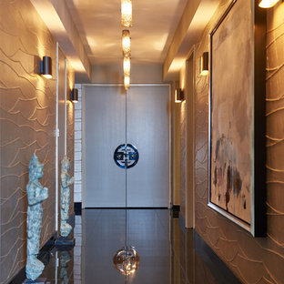 Example of a mid-sized trendy granite floor and brown floor entryway design in Los Angeles with metallic walls