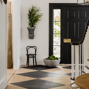 片開きドアトランジショナルスタイルのおしゃれな玄関ドア (白い壁、塗装フローリング、黒いドア) の写真