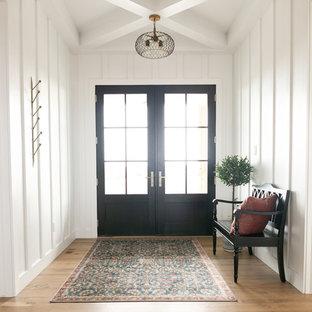 Idéer för mellanstora lantliga foajéer, med vita väggar, mellanmörkt trägolv, en dubbeldörr, en svart dörr och brunt golv