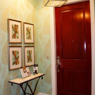 マイアミの中くらいの片開きドアビーチスタイルのおしゃれな玄関ラウンジ (緑の壁、トラバーチンの床、濃色木目調のドア) の写真