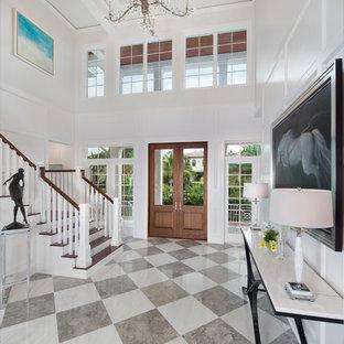 マイアミの広い両開きドアトロピカルスタイルのおしゃれな玄関ロビー (セラミックタイルの床、木目調のドア) の写真