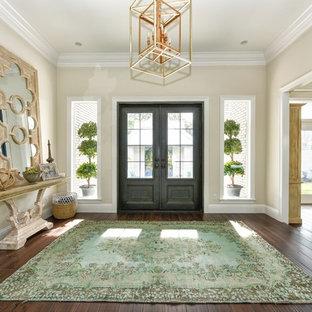 Cette photo montre un grand hall d'entrée chic avec un mur beige, un sol en bois foncé, une porte double, une porte grise et un sol marron.