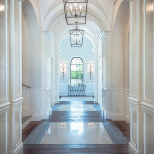 Example of a large tuscan dark wood floor and brown floor entryway design in Miami with white walls