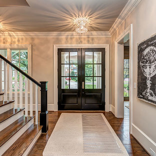 Elegant medium tone wood floor entryway photo in Charlotte with gray walls and a glass front door