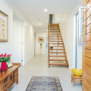 Photo of an asian foyer in Adelaide with white walls, a single front door, a medium wood front door and grey floor.