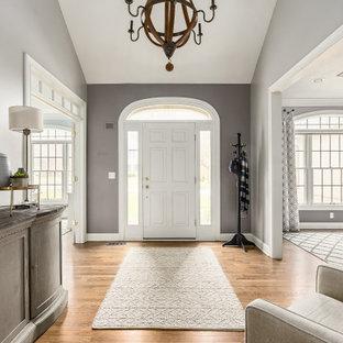 Aménagement d'un hall d'entrée classique avec un mur gris, un sol en bois brun, une porte simple, une porte blanche, un sol marron et un plafond voûté.