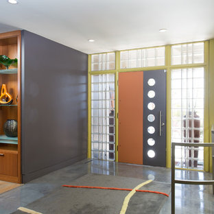 60 tals inredning av en mellanstor ingång och ytterdörr, med grå väggar, betonggolv, en enkeldörr, en orange dörr och grått golv