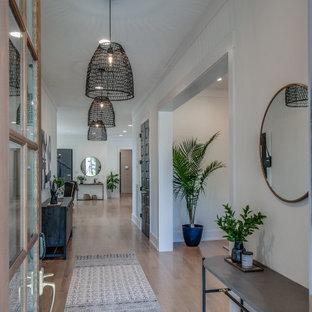 ナッシュビルの広い片開きドアコンテンポラリースタイルのおしゃれな玄関ホール (白い壁、淡色無垢フローリング、茶色いドア、ベージュの床) の写真