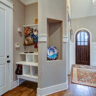Idee per un ingresso con vestibolo tradizionale di medie dimensioni con pareti grigie, pavimento in legno massello medio, una porta singola e una porta in legno scuro