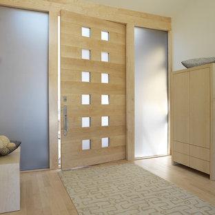 Diseño de puerta principal contemporánea, de tamaño medio, con puerta simple, puerta de madera clara, paredes blancas y suelo de madera clara