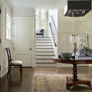 Идея дизайна: большое фойе в классическом стиле с белыми стенами, темным паркетным полом, одностворчатой входной дверью и входной дверью из темного дерева
