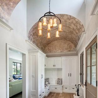 Inspiration för klassiska entréer, med beige väggar, ljust trägolv, en enkeldörr och en brun dörr
