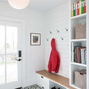 シアトルの片開きドアカントリー風おしゃれなマッドルーム (白い壁、ガラスドア、マルチカラーの床) の写真