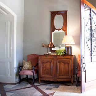 Immagine di un ingresso o corridoio country con una porta in legno bruno e pareti grigie