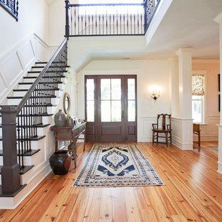 Свежая идея для дизайна: фойе среднего размера в стиле неоклассика (современная классика) с белыми стенами, темным паркетным полом, одностворчатой входной дверью и коричневой входной дверью - отличное фото интерьера