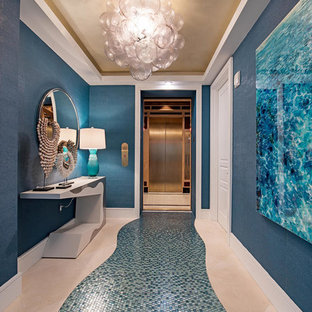 Example of a large coastal blue floor entry hall design in Miami with blue walls