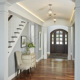 グランドラピッズの片開きドアビーチスタイルのおしゃれな玄関ロビー (グレーの壁、無垢フローリング、茶色いドア、折り上げ天井、茶色い床) の写真