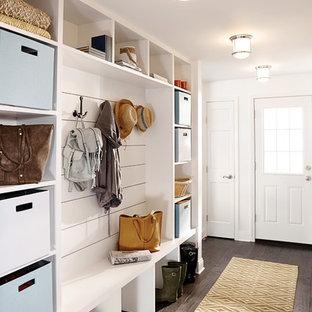 Ispirazione per un ingresso o corridoio chic con pareti bianche, parquet scuro, una porta singola, una porta bianca e pavimento marrone