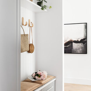 This is an example of a contemporary mudroom in Melbourne with white walls, medium hardwood floors and brown floor.