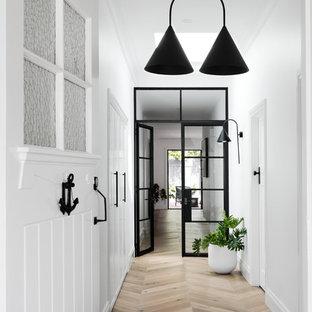 Inredning av en modern ingång och ytterdörr, med vita väggar, mellanmörkt trägolv, en enkeldörr, en vit dörr och brunt golv