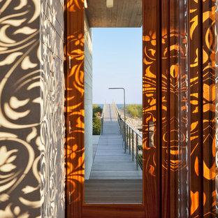 Idée de décoration pour une porte d'entrée marine avec une porte simple, une porte en verre, un mur marron, un sol en bois brun et un sol marron.