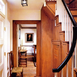 Entry hall - small shabby-chic style medium tone wood floor and brown floor entry hall idea in New York with brown walls and a white front door