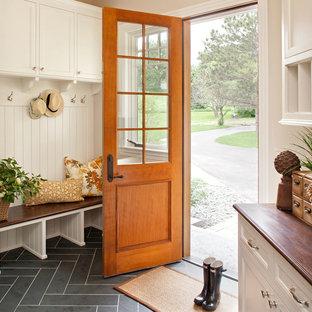Cette image montre une entrée traditionnelle de taille moyenne avec un vestiaire, un mur beige, un sol en ardoise, une porte simple et une porte en bois brun.