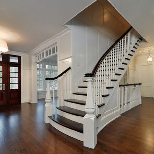 Cette image montre un très grand hall d'entrée traditionnel avec un mur blanc, un sol en bois foncé, une porte simple, une porte en bois foncé, un sol marron, un plafond à caissons et du lambris.