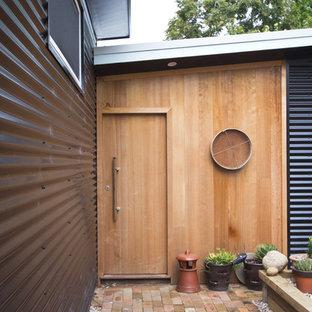 Entryway - industrial entryway idea in Sydney with a light wood front door and black walls